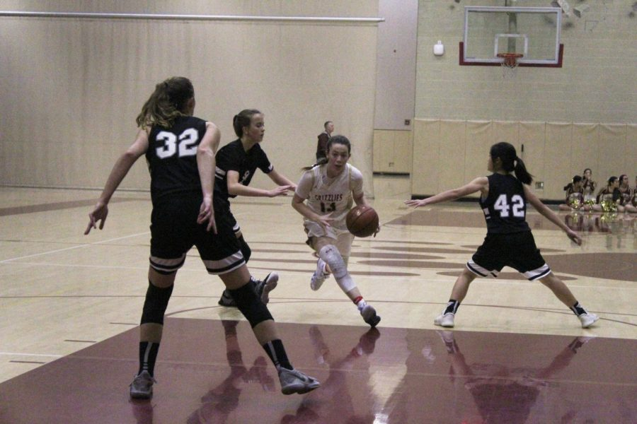 Catherine Beus (12) dribbles past her defenders for the shot.