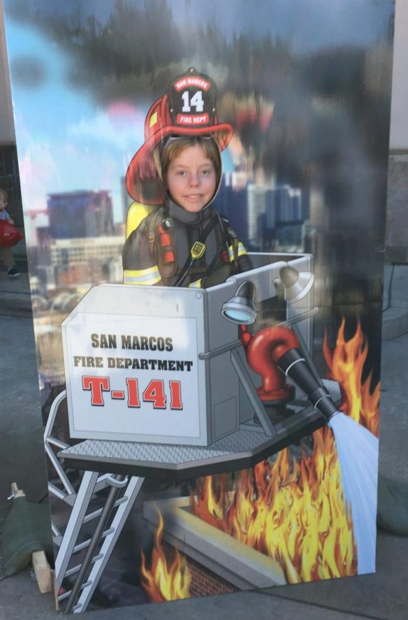 Abby Larson (11) smiles as she learns about firefighting equipment.