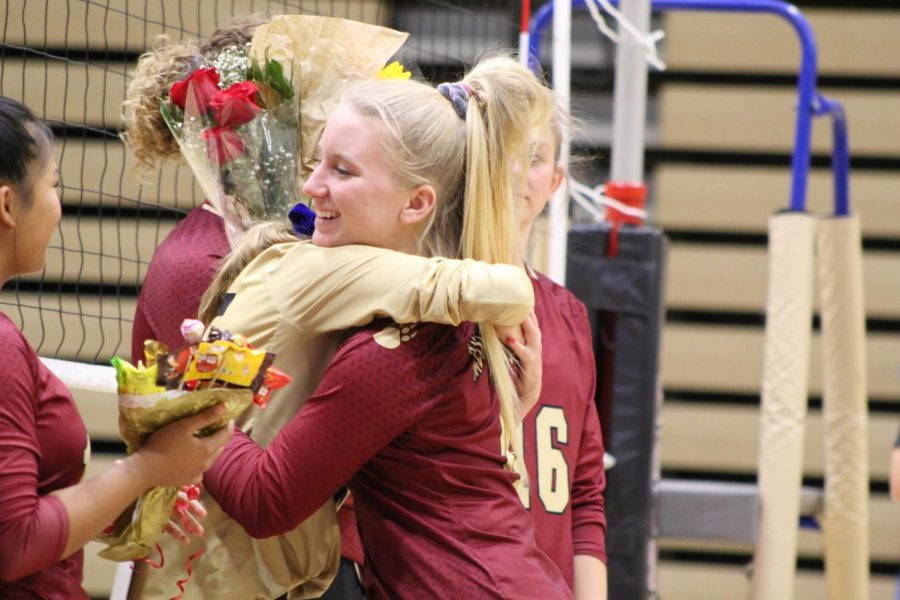 Volleyball player Jordan DeBlassio (12) hugs her teammates as she is recognized during senior night.