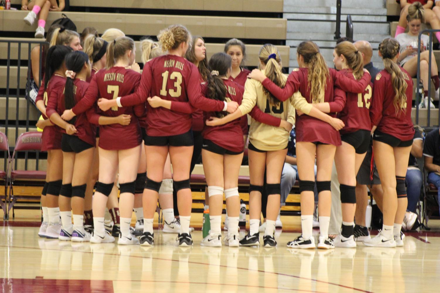 The varsity volleyball girls embrace as a team and prepare to head on the court for their game against La Costa Canyon.