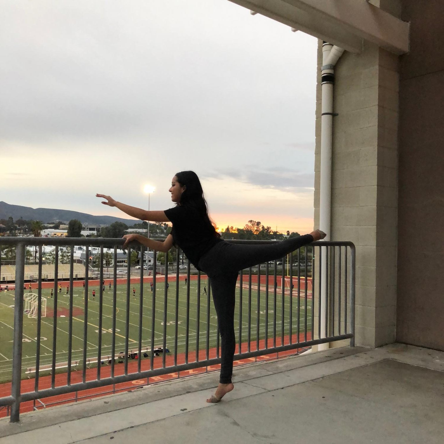 Noemi Aguilar (12) stretching in front of the sunset.
