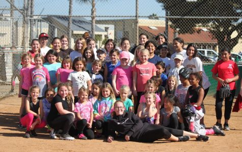 The softball team volunteers at a clinic to help aspiring young players