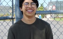 Boy standing in front of fence laughing