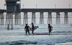 A group of surfers enjoying the waves at Oceanside Pier.