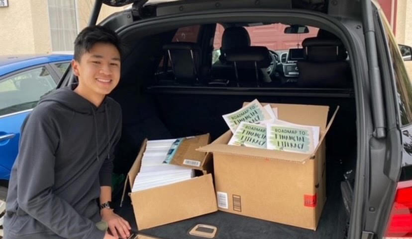 Andrew Diep-Tran standing next to boxes of financial literacy books that he plans to donate on behalf of his non-profit.