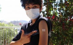 A student stands outside pointing towards a band-aid on their arm to show that they have their COVID-19 vaccine.