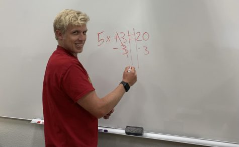 Mr. Krahel is solving an algebra problem on a whiteboard.