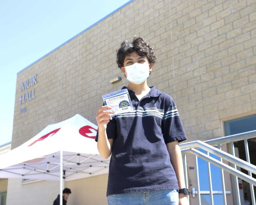 A student holds up their vaccination card