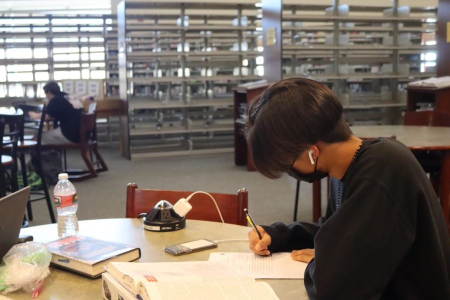 Tommy Nguyen listens to music to help him focus while he catches up on schoolwork.